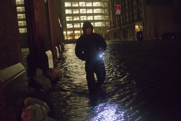 A security guard walks through a flooded street in the financial district of Manhattan, New York, Oct. 30