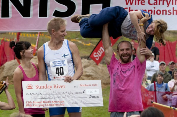 Jesse Wall of South Paris lifts Christine Arsenault after their second-place finish in the 2012 North American Wife Carrying Championship, Saturday, Oct. 6, 2012, at the Sunday River Ski Resort in Newry. The winners, Taisto Miettinen and Kristina Haapanen of Finland, hold a check for $530.