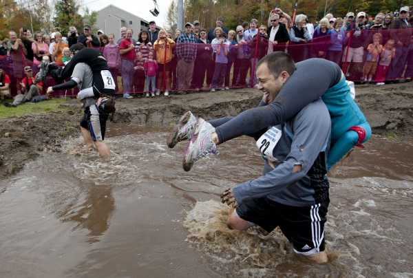 Chad Mars, of Cambridge, Mass., grimaces while carrying Caitlin Haynes through the water hazard during the 2012 North American Wife Carrying Championship, Saturday, Oct. 6, 2012, at the Sunday River Ski Resort in Newry, Maine.