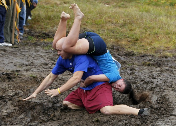 Arnie Lehto, of Boston, Mass., slips in the mud as Breanna Berry holds on during the 2012 North American Wife Carrying Championship, Saturday, Oct. 6, 2012, at the Sunday River Ski Resort in Newry, Maine.