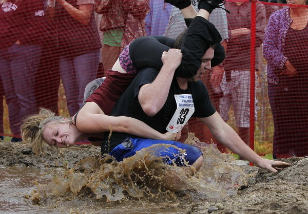 Avery McAllister of Belgrade, Maine, holds on as Zachary Atherton splashes through the water hazard during the 2012 North American Wife Carrying Championship, Saturday, Oct. 6, 2012, at the Sunday River Ski Resort in Newry, Maine.