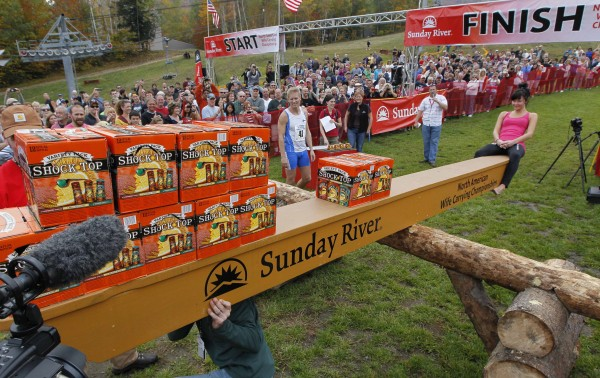 Kristiina Haapanen, Finland, sits at the end of a makeshift see-saw as she wins her weight in beer after she and Taisto Miettinen, of Finland won the 2012 North American Wife Carrying Championship, Saturday, Oct. 6, 2012, at the Sunday River Ski Resort in Newry, Maine.