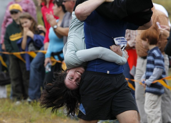 Amelia Kearon of Milford, N.H., holds on while being carried across an obstacle course by Ryan Banfield during the 2012 North American Wife Carrying Championship, Saturday, Oct. 6, 2012, at the Sunday River Ski Resort in Newry.