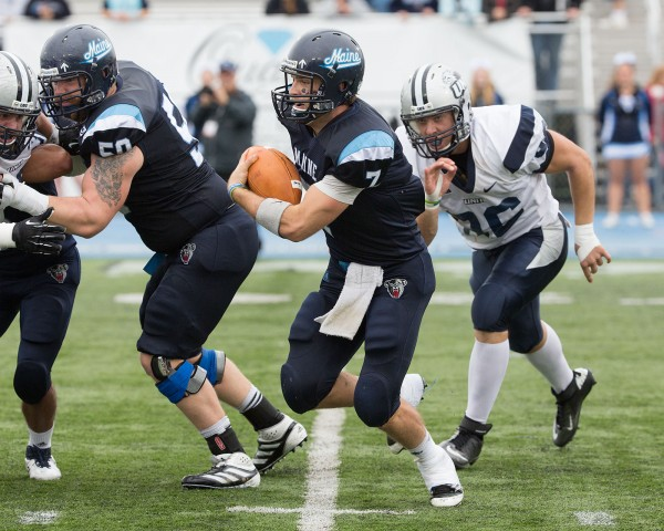 Marcus Wasilewski (7) scrambles out of the pocket under pressure from UNH's Cody Muller (96). UMaine's Chris Howley (50) blocks in the background.