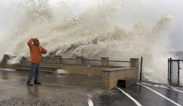 Waves crash over Eric Mongirdas as the storm surge caused by Hurricane Sandy pummels the coastline in Milford, Connecticut October 29, 2012. The monster storm bearing down on the U.S. east coast, strengthened on Monday after hundreds of thousands moved to higher ground.