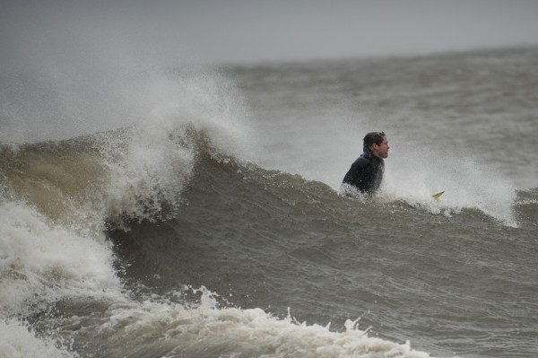 A surfer catches a wave along Coney Island in New York, October 29, 2012. Hurricane Sandy began battering the U.S. East Coast on Monday with fierce winds and driving rain, as the monster storm shut down transportation, shuttered businesses and sent thousands scrambling for higher ground hours before the worst was due to strike.
