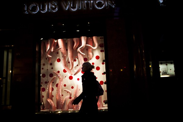 In this Sept. 26, 2012 photo, a woman walks by Louis Vuitton store at the Alvear Avenue, in Recoleta neighborhood in Buenos Aires, Argentina. The world's most luxurious designer brands are abandoning Argentina rather than complying with tight new government economic restrictions, leaving empty shelves and storefronts along the capital's elegant Alvear Avenue, where tourists once flocked to see the latest in fashion.