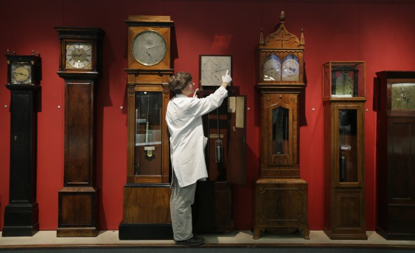 Conservator Richard Horton poses for the media as he adjusts a regulator clock by Cope and Molyneux, 1822-1823, one of the iconic clocks in the Science Museum's Measuring Time gallery, in London Friday, Oct. 26, 2012. On Sunday, Oct. 28 the clocks will go back and preparations are being put in place at the museum gallery, which traces the history of timekeeping from sand-glasses to sundials, water clocks to wristwatches, a rich collection of more than 500 timepieces from all eras.