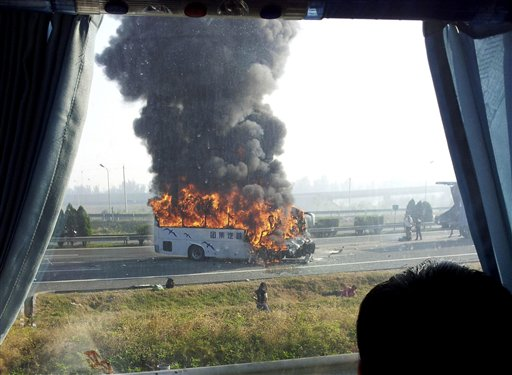 In this photo taken with a cellphone through a glass window of another vehicle and distributed by China's Xinhua News Agency, a tourist bus is engulfed in flames on an expressway near Tianjin, China on Monday, Oct. 1, 2012. Five Germans and a Chinese citizen were killed when the bus burst into flames after hitting the back of a truck, Xinhua said.