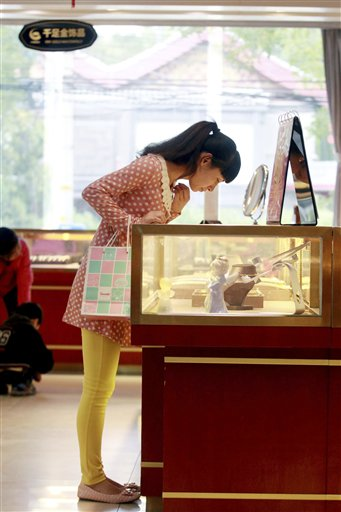 In this photo released by China's Xinhua News Agency, a customer selects gold jewelry at a shop in Beijing on Wednesday, Oct. 3, 2012. During the Mid-Autumn Festival and Chinese National Day holiday, which lasts from Sept. 30 to Oct. 7, also known as the &quotgolden week&quot, people in many places in China go to buy gold jewelry.