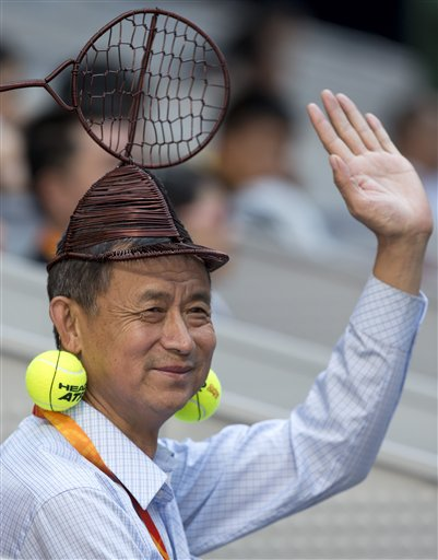 A Chinese man wears an iron-made tennis racquet-shaped hat and tennis ball ear rings while watching a match between Spain's Feliciano Lopez and Jo-Wilfried Tsonga of France in the men's singles semifinal match of the China Open tennis tournament in Beijing on Saturday, Oct. 6, 2012.