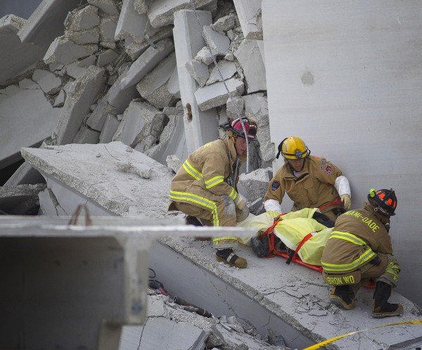 Fire Rescue officials work to remove a victim from the collapsed parking garage at the Miami Dade College West campus in Doral, Fla. Tuesday, Oct. 10, 2012. A section of a parking garage under construction at a community college collapsed killing one worker and trapping two others in the rubble, officials said. At least 10 other workers were hurt when the roof of the five-story concrete garage fell, creating a pancake-style collapse on the campus of Miami-Dade College, officials said.