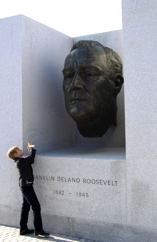 Felix von Perfall, 8, grandson of former U.S. Ambassador to the U.N. William vanden Heuvel, takes a picture of the bust of Franklin D. Roosevelt that is part of the new Franklin D. Roosevelt Four Freedoms Park, before the dedication ceremony in New York, Wednesday, Oct. 17, 2012. Celebrating a design 40 years in the making, dignitaries on Wednesday dedicated a new memorial park to President Franklin Roosevelt overlooking the United Nations that he helped found.