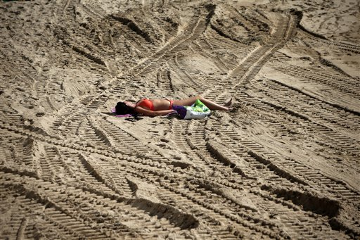 A woman sunbathes on the beach amid vehicle tracks in Cannes, southeastern France on Monday, Oct. 8, 2012.