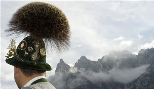 A participant of the Gamsbart Olympics in traditional clothes stands in front of the Karwendel Mountains near Mittenwald, southern Germany on Sunday, Oct 14, 2012. The Gamsbart (chamois beard), originally worn as a hunting trophy, is a tuft of hair worn as decoration in the alpine regions of Austria and Germany. It is made by enclosing the lower end of the tuft of hair in a setting of metal or horn that allows the upper end to spread in a brush-like fashion. The size and diameter of the Gamsbart are important signs of the wearer's pride.