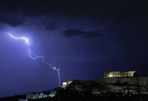 Lightning illuminates the ancient Parthenon temple atop the Acropolis hill in Athens on Sunday, Oct. 14, 2012. Greece is inching toward an agreement with its international debt inspectors as they struggle to hammer out the details of euro13.5 billion ($17.5 billion) in austerity measures for the next two years, a package essential for Greece to receive the next installment of its vital bailout funds.