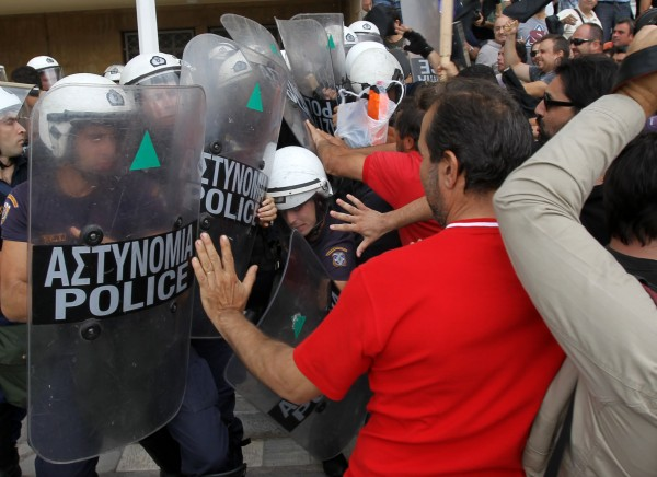 Riot police clash with protesters inside Greece's Defense Ministry in Athens, Thursday, Oct. 4, 2012. Police clashed with scores of protesting shipyard workers after they forced their way into the grounds of Greece's Defense Ministry. The workers say they have not been paid in months.