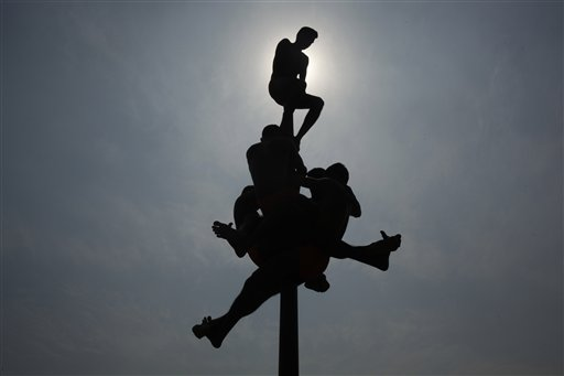 Indian army soldiers display their acrobatic skills as they perform &quotMalkhamb&quot a traditional sport during a two-day army exhibition in Allahabad, India on Sunday, Oct. 21, 2012.