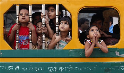 Indian children watch a Dussehra festival procession early morning in Allahabad, India on Sunday, Oct. 21, 2012. The Hindu festival Dussehra commemorates the triumph of Lord Rama over the demon king Ravana, marking the victory of good over evil.