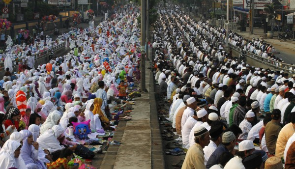 Muslim sit on a street as they attend Eid al-Adha prayer in Jakarta, Indonesia, Friday, Oct. 26, 2012. Muslims will later slaughter cattle and goats, with the beef and meat distributed to the needy in the holiday which honors the prophet Abraham for preparing to sacrifice his son Ishmael on the order of God, who was testing his faith.