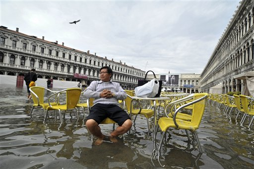 A tourist sits outside a cafe in flooded St. Mark square as high tides reached 1.05 meters above sea level, partly flooding the city of Venice, Italy on Monday, Oct. 15, 2012.