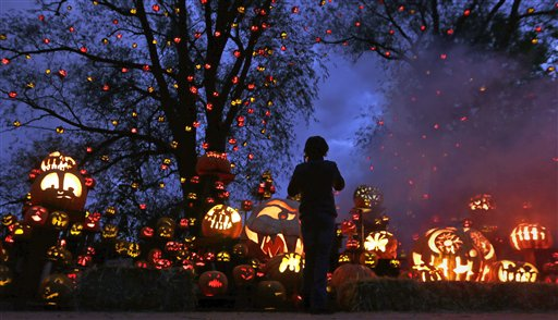 While surrounded by hundreds of pumpkins, a girl stops to look at the illuminating jack-o'-lanterns at the Roger Williams Park Zoo in Providence, R.I., Monday, Oct. 8, 2012. Some 5,000 carved pumpkins are on display for this year's Jack-o'-lantern Spectacular, one of the nation's largest jack-o'-lantern shows.