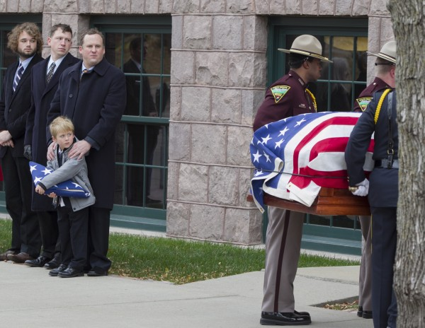 Will Mead holds a tri-folded flag as he watches with family members the casket of his great grandfather, former Democratic U.S. Senator and three-time presidential candidate George McGovern, being carried into the Washington Pavilion of Arts and Science in Sioux Falls, S.D., for the funeral service, Friday, Oct. 26, 2012. McGovern died Sunday in his native South Dakota at age 90.