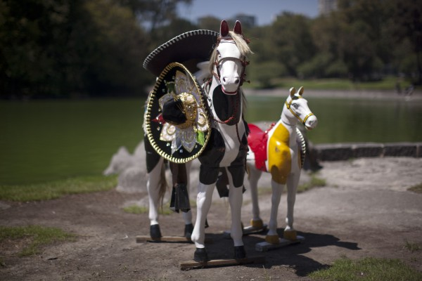 Life size toy horses that are used as props by a street photographer stand along Chapultepec Lake in Mexico City, Thursday, Oct. 4, 2012. Tourists pose with the horses for souvenir portraits.