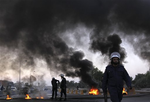 Riot police extinguish burning tires set by Bahraini anti-government protesters (unseen) near oil pipelines that connect to neighboring Saudi Arabia along a highway in Buri, Bahrain, on Thursday, Oct. 11, 2012. Protesters often block roads with burning tires to highlight their demands for the release of political prisoners and democracy in the Gulf island kingdom.