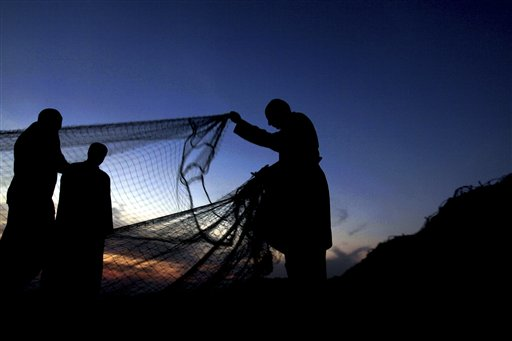 Bahraini fisherman Sayed Hashem Sayed Mohamed, 62, (right) prepares his nets at dusk in Malkiya, Bahrain, on Saturday, Oct. 13, 2012, readying them for more early morning fishing in the Persian Gulf.