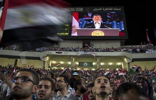 Egyptian President Mohammed Morsi is seen on a large screen as he speaks to a packed stadium on the 6th of October national holiday marking the 1973 war with Israel, Cairo, Egypt on Saturday, Oct. 6, 2012.