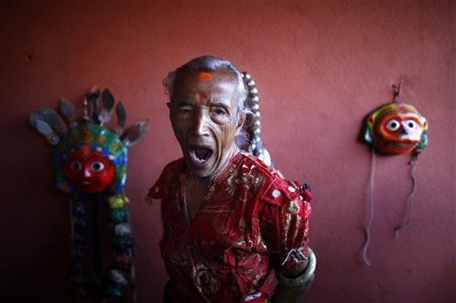 A Nepalese mask dancer yawns as he gets ready for Shikali festival in Khokana, outskirts of Katmandu, Nepal on Sunday, Oct. 21, 2012. Devotees sacrifice animals hoping to get the blessing of deities during this festival.