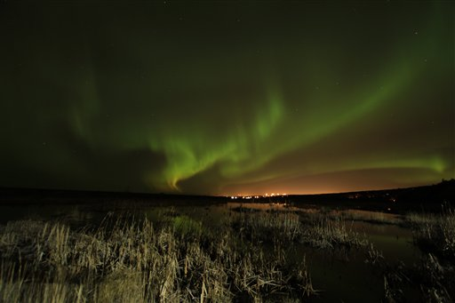 Northern lights illuminate the sky over Potter Marsh (foreground) and in the distance in Anchorage, Alaska on Saturday, Oct. 13, 2012 shortly after midnight.