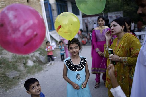 Pakistani neighbors of bride Shabana Gill, 20, (not pictured) wait her arrival outside a church during her wedding in a Christian neighborhood in Islamabad, Pakistan on Friday, Oct. 5, 2012.
