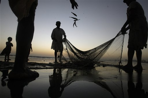 Pakistani fishermen pull their net out of the sea onto the beach in Karachi, Pakistan on Monday, Oct. 8, 2012.