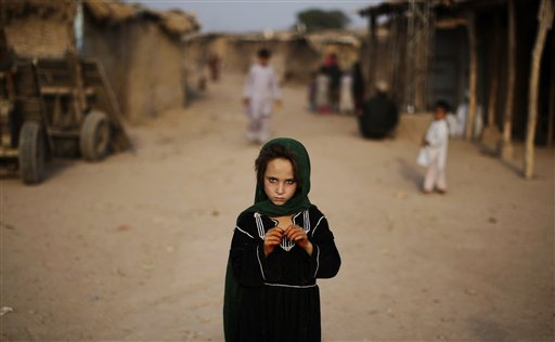 Afghan refugee Naseema Zurab, 7, stands in a slum on the outskirts of Islamabad, Pakistan on Friday, Oct. 12, 2012.