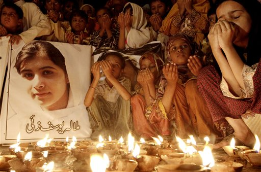 Pakistani children pray for the recovery of 14-year-old schoolgirl Malala Yousufzai, who was shot on Tuesday by the Taliban for speaking out in support of education for women, during a candlelight vigil in Karachi, Pakistan on Friday, Oct. 12, 2012. A Pakistani military spokesman says Yousufzai is in &quotsatisfactory&quot condition but cautions that the next few days will be critical. Writing reads on the poster left, &quotMalala Yousufzai.&quot