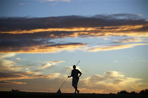 A caddie stands with the flag of the 9th hole during the first round of the Portugal Masters golf tournament at the Victoria golf course in Vilamoura, southern Portugal, Thursday, Oct. 11, 2012.
