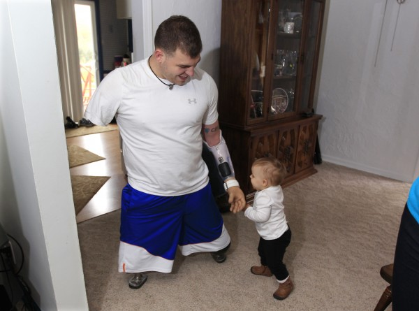 Army Staff Sgt. Travis Mills plays with his daughter Chloe in his boyhood home in Vassar, Mich., Thursday, Oct. 4, 2012. Mills is visiting his hometown for the first time since losing all four limbs while fighting in Afghanistan. Mills, his wife, Kelsey, and their 1-year-old daughter, Chloe, will be the grand marshals of Vassar High School's homecoming parade on Thursday evening.