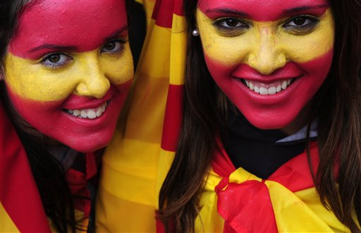 Two girls with their faces painted with the colors of the Spanish flag pose to photographers during the holiday known as Dia de la Hispanidad, Spain's National Day in Barcelona, Spain on Friday, Oct. 12, 2012.  Spain is in recession and under pressure to fix its finances while celebrating the day Christopher Columbus discovered America in the name of the Spanish Crown.