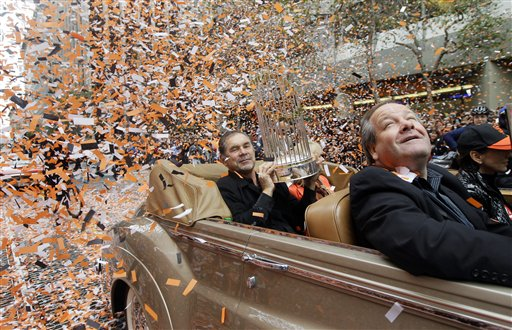 San Francisco Giants manager Bruce Bochy holds the World Series trophy as confetti falls during the baseball team's World Series victory parade, Wednesday, Oct. 31, 2012, in San Francisco.