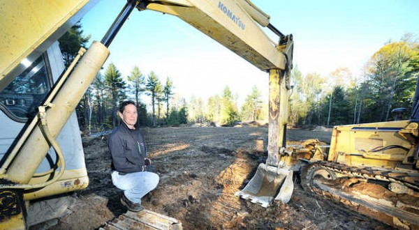 Michelle Melaragno stands recently with heavy equipment at her animal compost facility under construction on Trapp Road in Auburn.