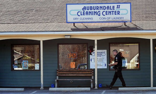 Auburn's Sgt. Barry Schmieks walks in front of Auburndale II Cleaning Center after a masked man robbed Taylor Brook Mall storefront early Friday afternoon.