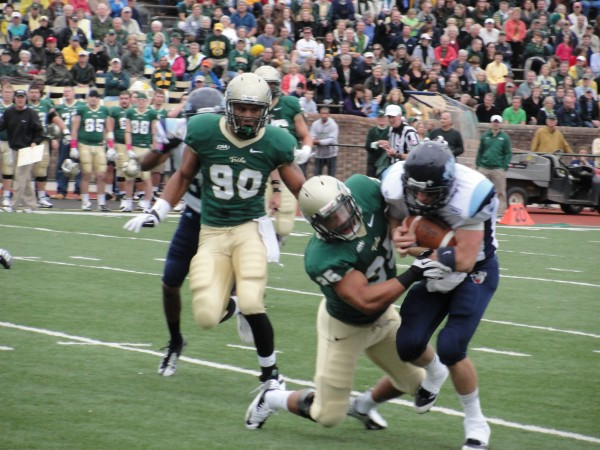University of Maine quarterback Marcus Wasilewski is pulled down by William & Mary linebacker during Saturday's CAA game in Williamsburg, Va.