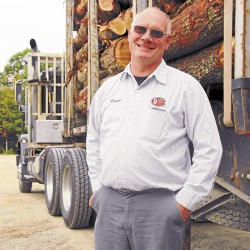 Duane Jordan stands beside a loaded log truck parked in the yard of his Waltham-based company, Elliott Jordan & Son. The company was started by Jordan's grandfather and then owned by his father, Marshal, before he took the reins in the 1980s.