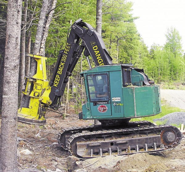 An employee of Elliott Jordan & Son operates a feller-buncher while harvesting trees in Township 16 in Hancock County.