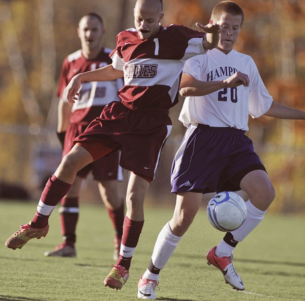 Hampden boy's soccer player Ben Foster (20) works the ball away from Edward Little player Luke Sterling (1) in the first half of their game in Hampden, Maine, Wednesday, Oct. 24, 2012.