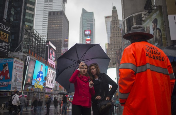 Visitors hold umbrellas while taking photos during rainfall at Times Square in New York October 29, 2012. Category 1 storm Hurricane Sandy was strengthening and the center of the storm was forecast to move over the coast of U.S. mid-Atlantic states by Monday night, the U.S. National Hurricane Center said on Monday.