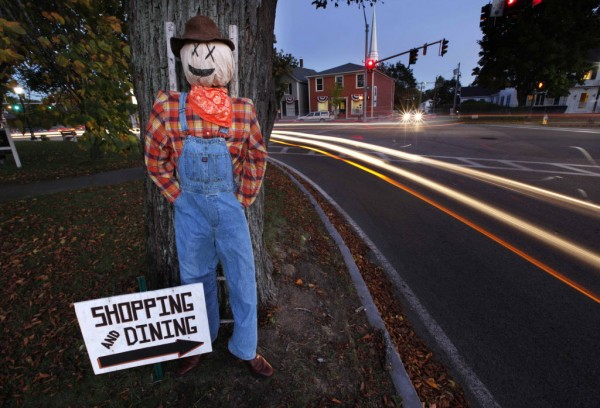 A pumpkin-headed farmer stands outside the public library as evening traffic streaks by on Fletcher Street in Kennebunk.