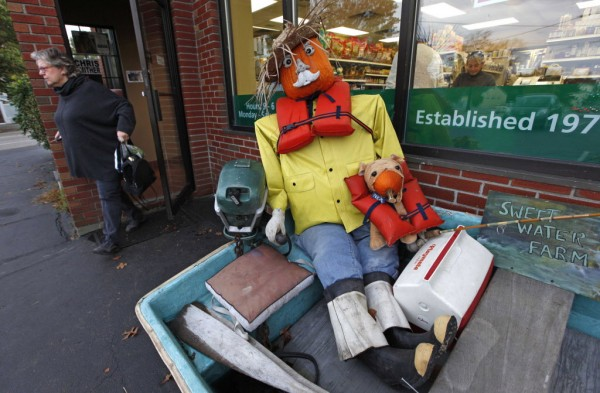 A fisherman and his dog sit in a dinghy outside the New Morning Natural Food store in Kennebunk.